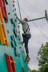 Nick Evans, trainee data engineer, tackling the climbing wall.